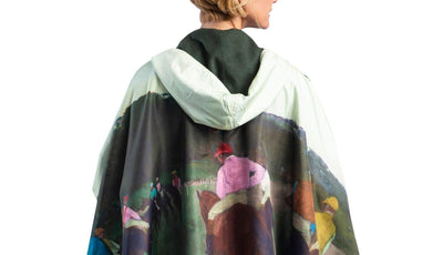 Woman wearing a WarmCaper Degas Racehorses at Longchamp rain and travel cape. The reversible cape is black; the Degas Racehorses at Longchamp print is visible on the hood and cuffed arms.