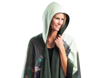 Woman wearing a WarmCaper Degas Racehorses at Longchamp hooded rain and travel cape which reverses to a warm loden green.
