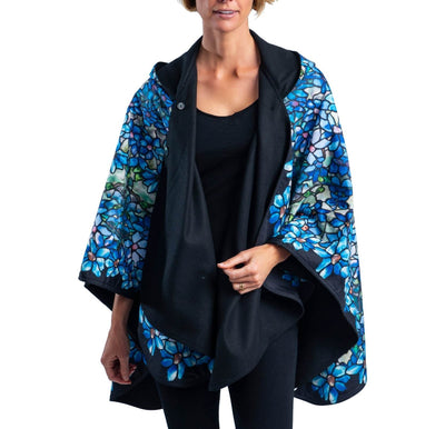 Woman wearing a WarmCaper Tiffany Clematis lined rain and travel cape by RainCaper. The rainproof side features a Tiffany Clematis print while the warm side is black.