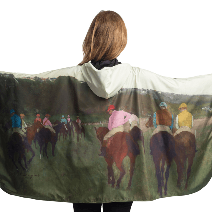 Woman wearing a RainCaper Degas Racehorses at Longchamp travel cape.