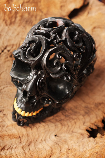 Ebony woodcarving of human skull with Balinese motif and ox-bone teeth