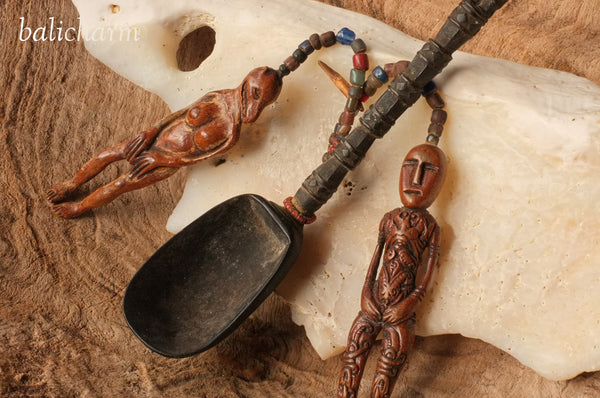 Traditional, antique wooden ladle from Indonesian Timor with amulets carved from ancient mammoth ivory