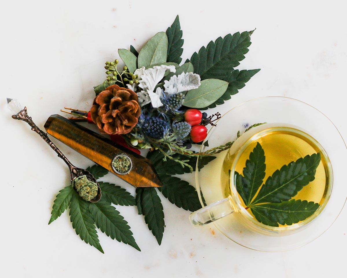 Cannabis display with leaves, fruits, and crystal/wooden pipes