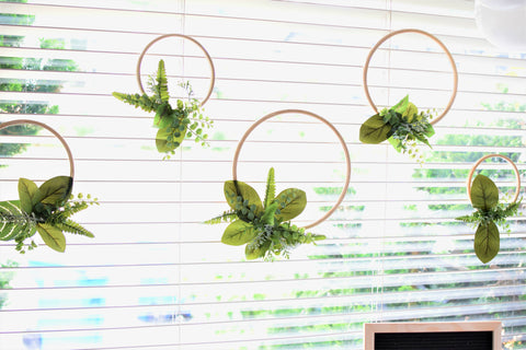 greenery covered embroidery hoops hanging from window behind dessert table blog post by sweet chubby cheeks