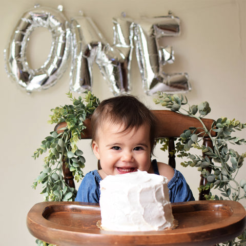 silver one letter balloon set for a first birthday cake smash in wood highchair. blog post by sweet chubby cheeks