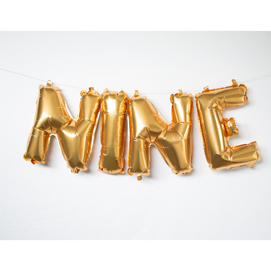 gold letter balloons spelling nine by sweet chubby cheeks