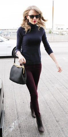 Taylor Swift wears a black Turtle Neck T shirt with brown pants and boots.