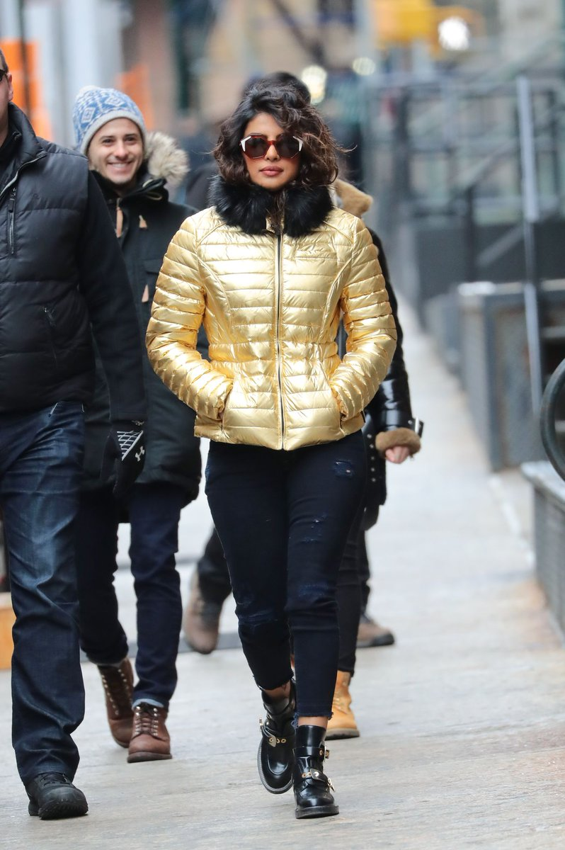 a Golden quilted jacket with black pants and black boots