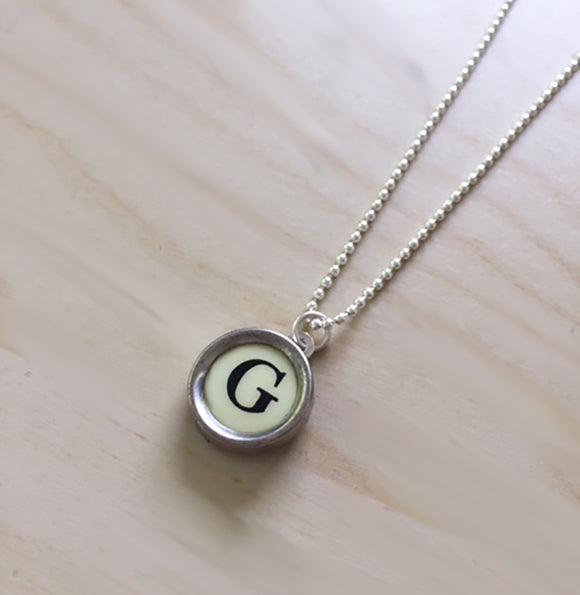 Letter G Sterling Silver Typewriter Necklace on Light Background