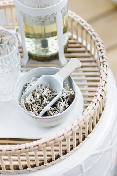 A bowl full of sage leaves with a scooper on a wicker platter.