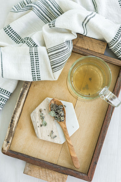 Wooden spoon full of sage tea, a tea cup full of tea, and a textured tea towel on top of a wooden platter.