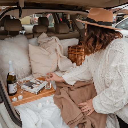 Women setting up a picnic in back of car