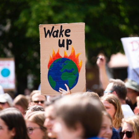 Protest sign from a Climate March saying 'Wake Up' with an image of a burning Earth