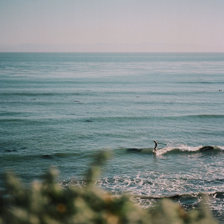 Horizon view of the ocean at dusk with a single surfer in the waves