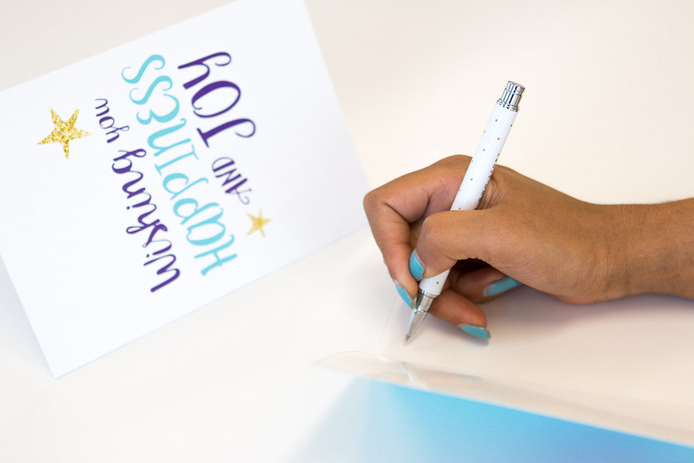 Hand holding pen and writing in printed Starlight Christmas Card