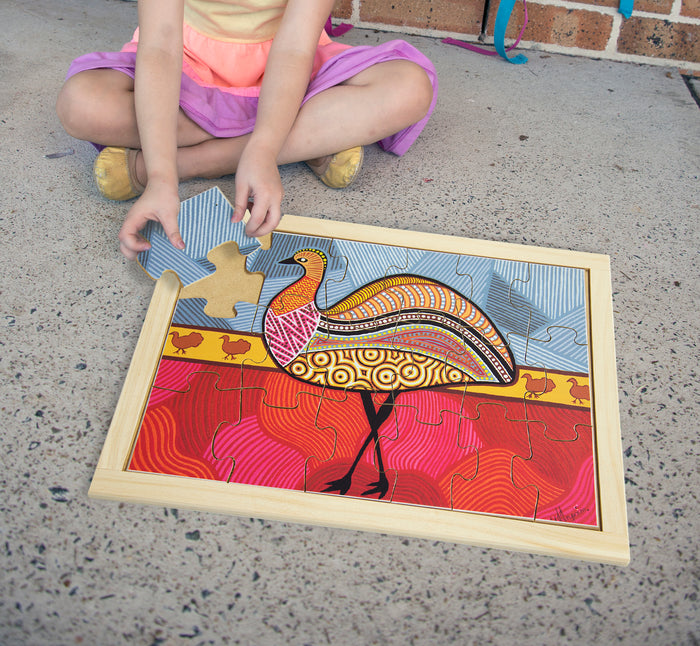 Young girl playing with 'aboriginal art emu' wooden jigsaw puzzle