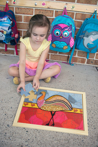 child playing with an education national oz publishing jigsaw puzzle