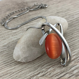 Orange cats eye pendant with silver swirl