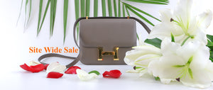 gray hermes constance with gold hardware. Side with white and red flowers and leaves