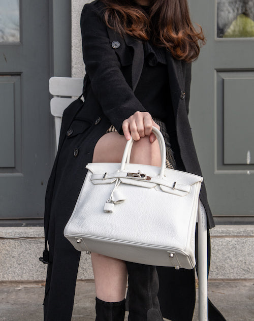a female model holds a Hermes Birkin Clemence 30 White Leather