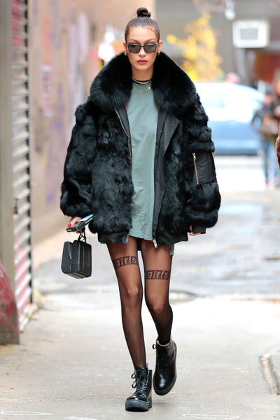 2e71b7b0279 ... Bella Hadid paired lace up boots and sheer tights with a statement  oversized fur jacket for the ultimate grunge look. She added simple silver  hoops