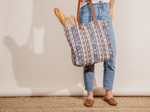 Young woman holding a farmer's market tote with bread in it.