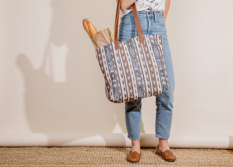 Lower half on women holding farmer's market tote on her forearm with bread and groceries inside. Wearing blue jeans and flat sandals with a white background and tan floor.