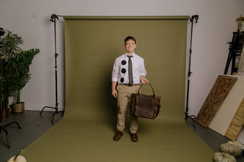 young man dressed up as Jim from The Office for Halloween with a Nena & Co. leather bag