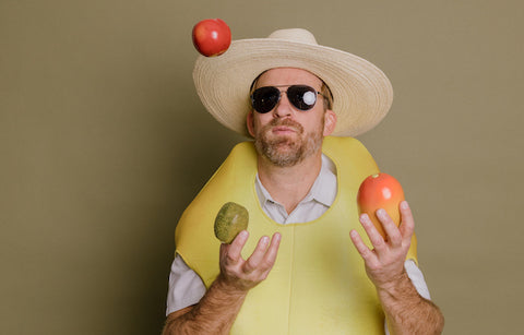 a man juggling fruit while wearing a banana costume and  straw hat