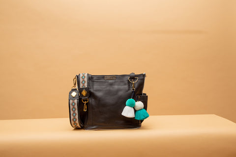 All leather Nena & Co. bag with a Kenya strap and pom demonstrating the add-on system.