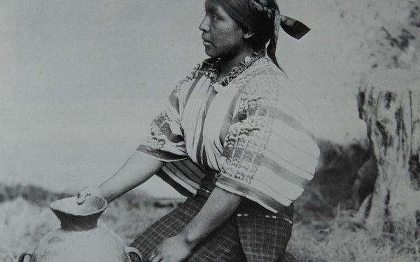 A black and white image of an indigenous woman in Guatemala on her knees, side profile, and holding a pot.