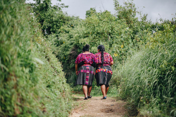 Two indigenous Maya women in their huipiles and cortes walking through the Guatemala forest