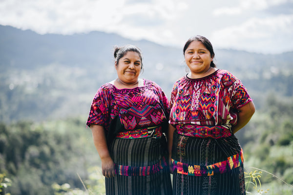 Two Guatemalan Women taking a picture in front of a landscape of trees and mountains