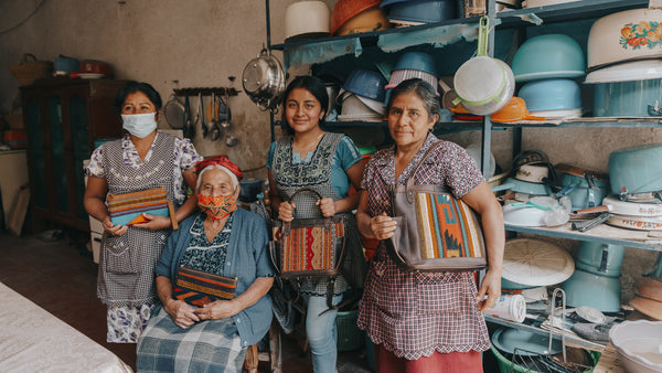 Four Guatemalan women taking a picture holding the bags with the textiles they handmade on them for Nena & Co.