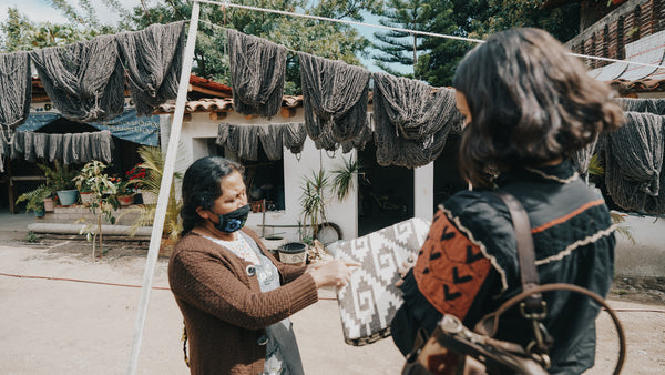 A Guatemalan woman talking with Ali Hynek, the CEO and Founder, of Nena & Co. about some rugs.