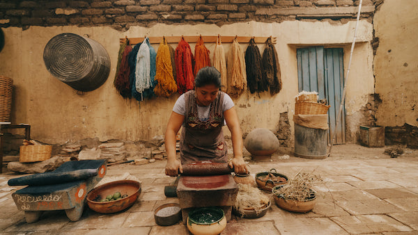 An Artisan working on crushing natural items to create colors that will be used to dye wool. She has all different colors of wool behind her hanging on the wall.