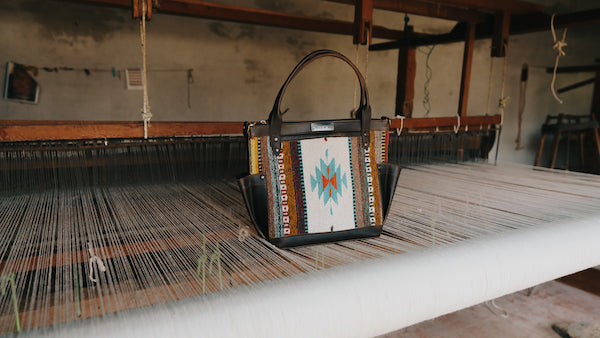A beautiful Nena & Co. handbag from the Mexico Collection sitting on top of a footloom used to create textiles.