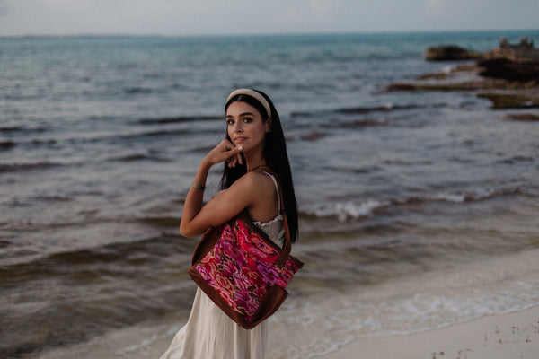 Young woman in a dress holding a Nena & Co. bag made of upcycled huipils on her shoulder on the beach.