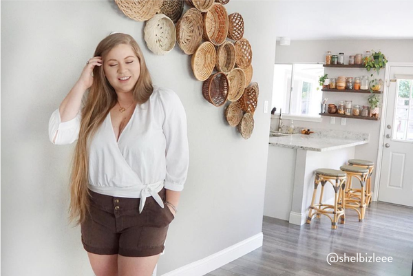 Female posing in her house for a photo standing straight and tucking her hair behind her ear