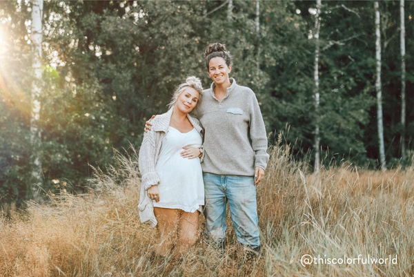 A same sex female couple posing for a photo with pine trees behind them. One woman is pregnant.