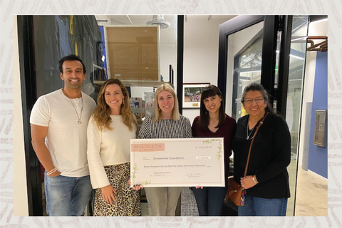A photo of Nena & Co. giving a donation to the Dressember foundation.