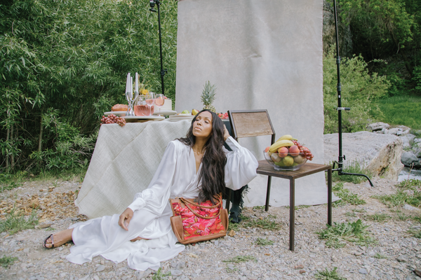 A beautiful black female model laying on the ground princess-style with her chin tilted up and eyes closed. There is a table with fruits and foods behind her and a backdrop behind the table.