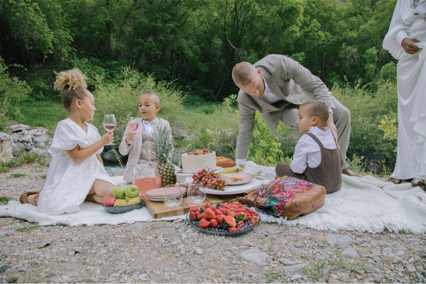 A biracial family sitting down together for a picnic in them mountains by a river.