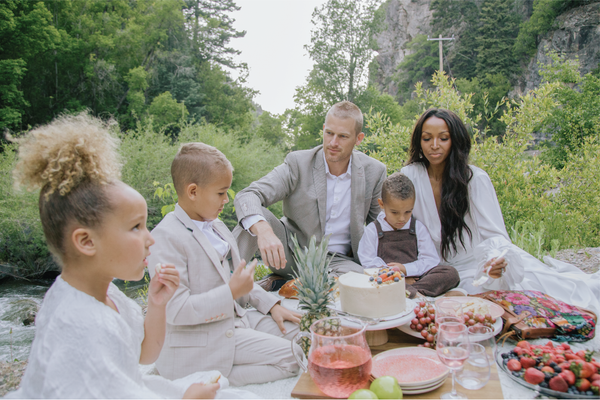 A biracial couple with three children having a picnic in nature celebrating Juneteenth