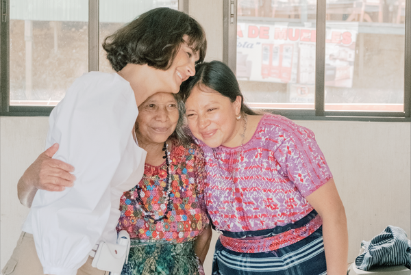 Ali Hynek, CEO fo Nena & Co. hugging two Guatemalan female Artisans in front of some windows inside a house.