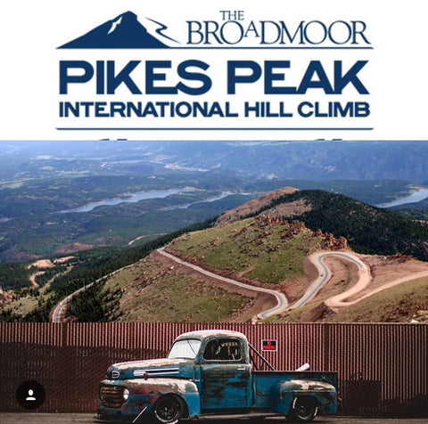 Chuckles Garage's 1949 F1 Farm Truck sits in profile in front of a graphic of the sprawling Pike's Peak track under a graphic for the Pike's Peak logo.