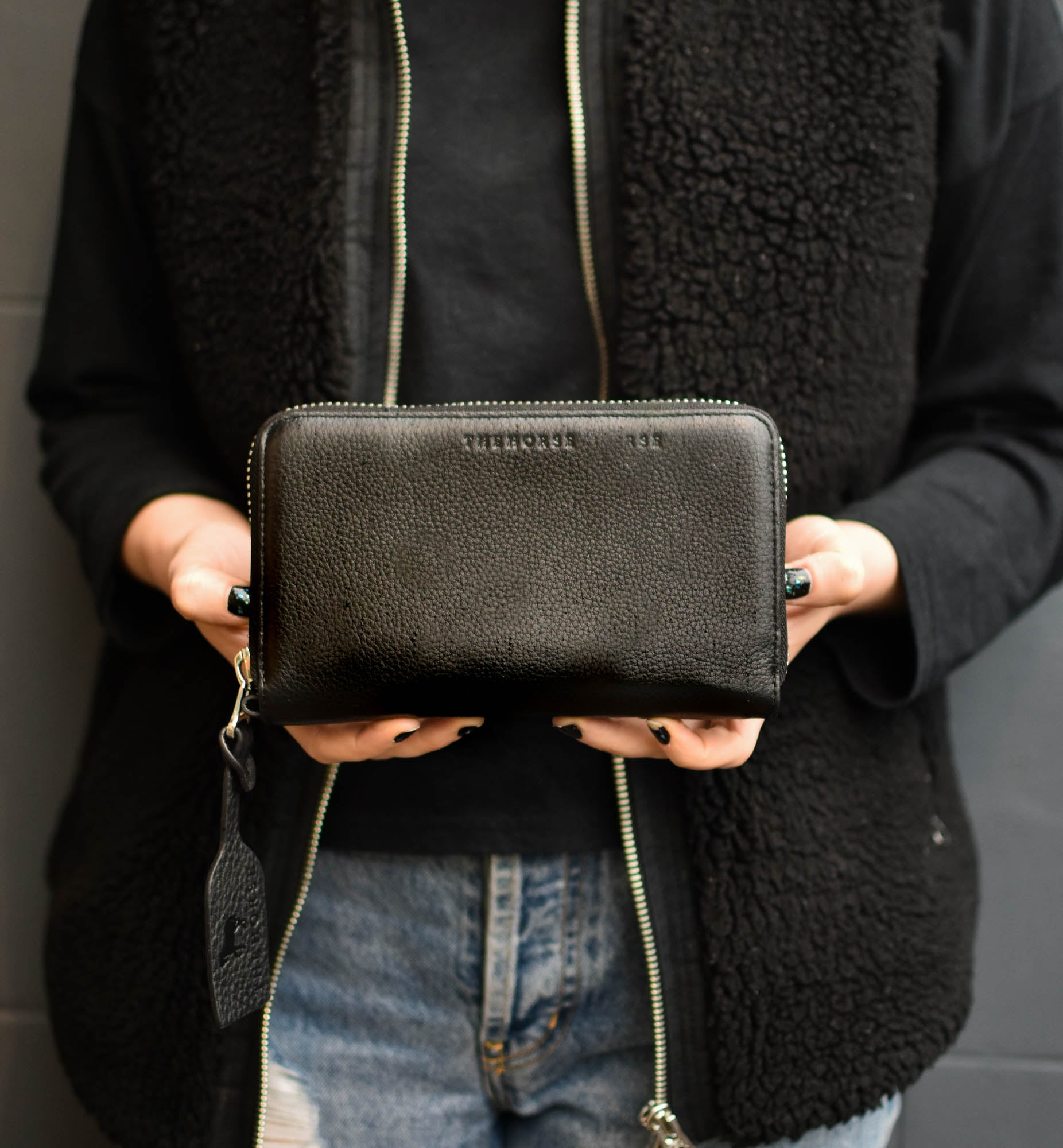woman standing holding black wallet