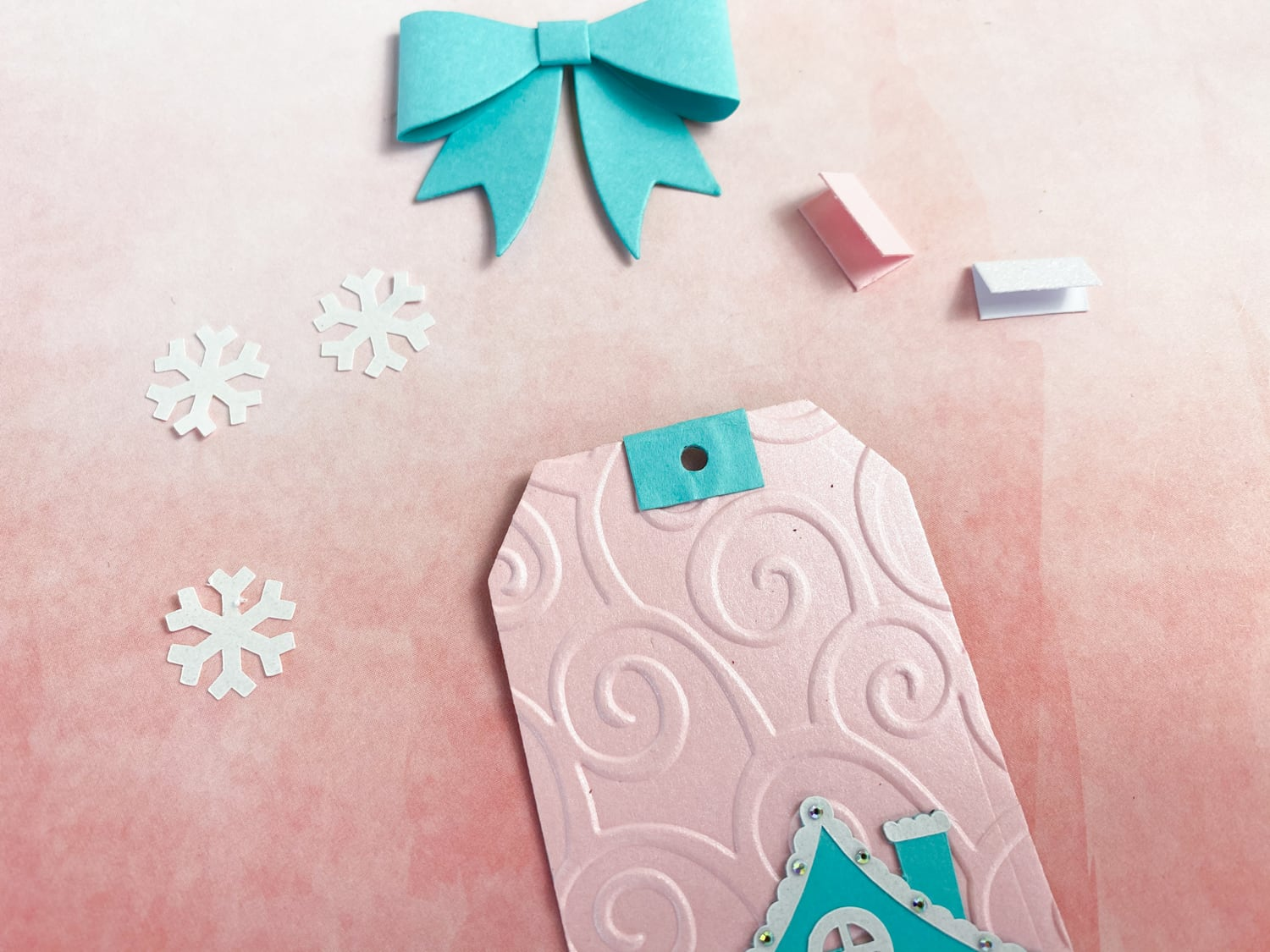 adding bow to top of gingerbread house holiday tags