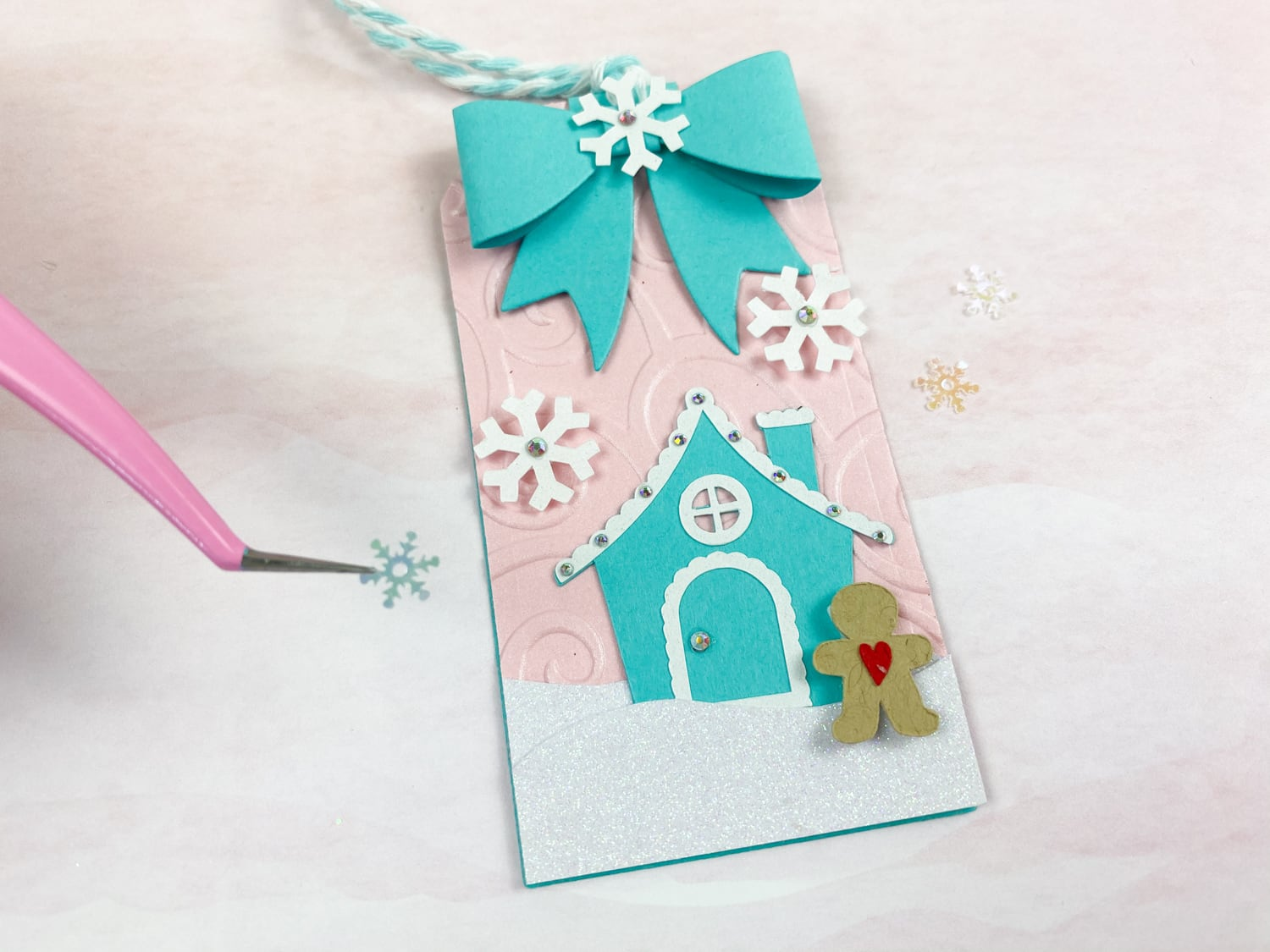 adding final embellishments to gingerbread house DIY tags
