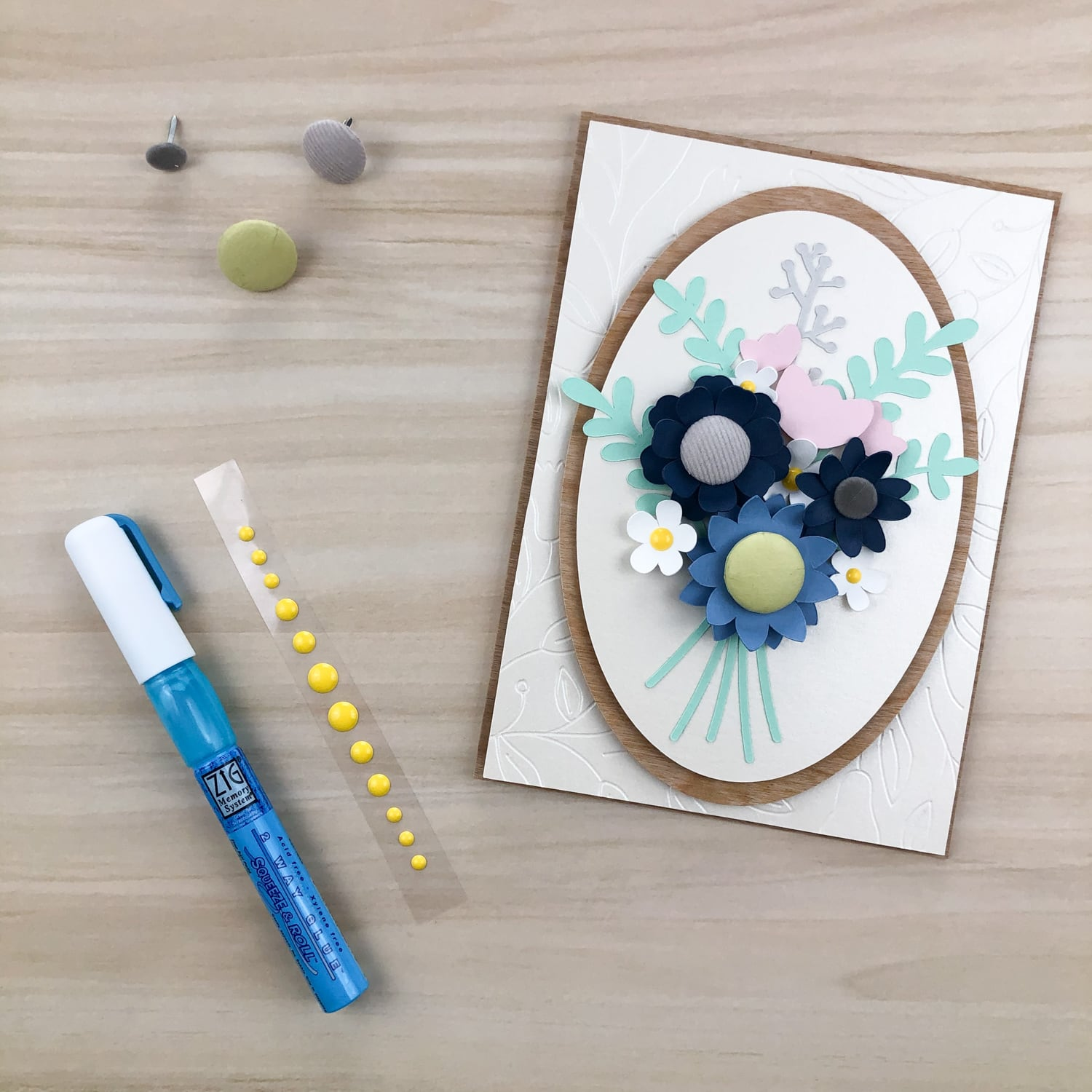 adding brads and enamel dots to centers of paper flowers